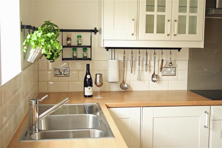 Красивая контрастная столешница в белой классической кухне светлых оттенков