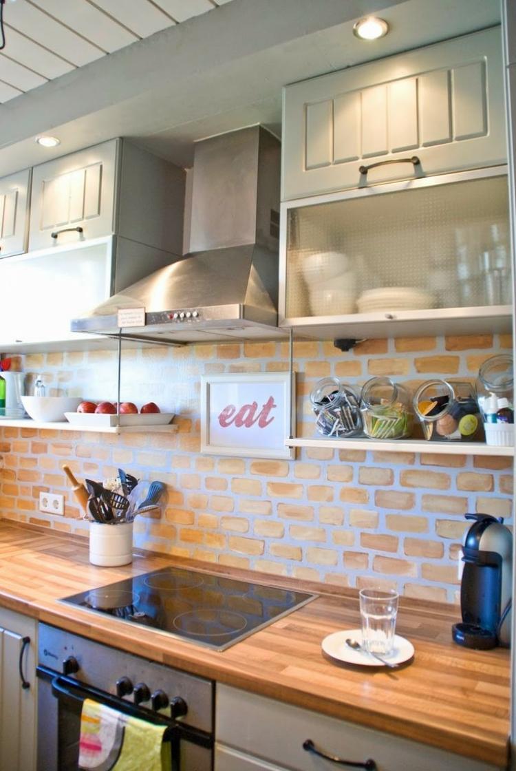 Светлая кухня с отделкой стеновой панели из камня дополнена идеальной деревянной столешницей